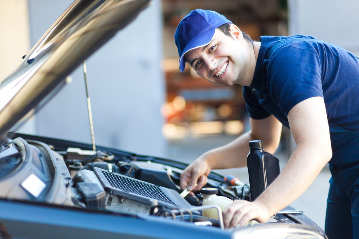 Mechanic working on car and smiling